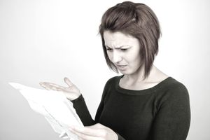 Woman looking at a credit card statement with expression of disbelief