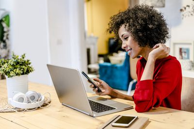 Woman on computer with cell phone