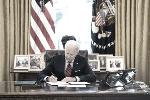 Joe Biden sits in the oval office signing a document