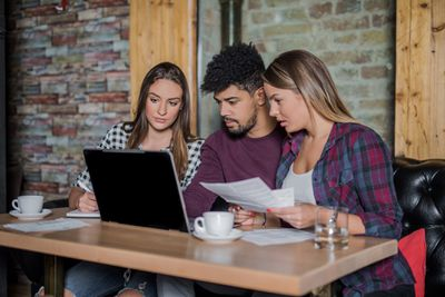 Group of young people using a laptop to research student loans.