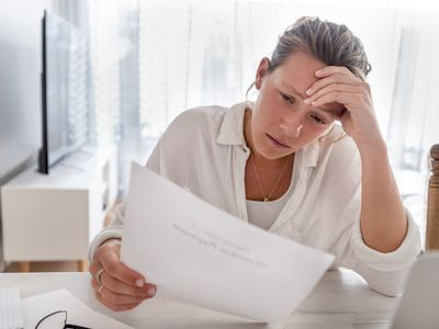 Woman looking worried holding paperwork at home. She is reading a financial bill or a letter with bad news. She looks very stressed and upset. There is a laptop computer on the table.