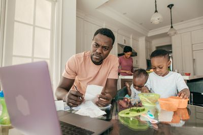 A husband deals with finances on a computer while children play, and his wife cooks in the background