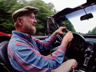 Smiling older man behind the wheel of a convertible
