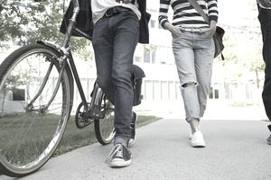 College students walking on campus with one pushing a bike