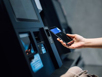 Close up of a young Asian woman using contactless payment via smartphone to pay for her shopping at self-checkout kiosk in a store