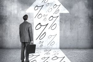 Man looking at increased percentages, represented by an arrow pointing up filled with percent signs.
