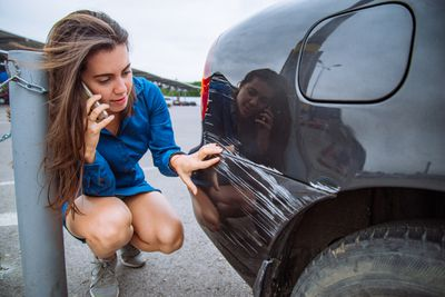 Woman making a phone call about damage on her car