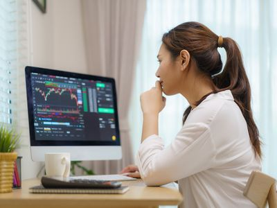 A person at a desk looking at currency spread charts on computer
