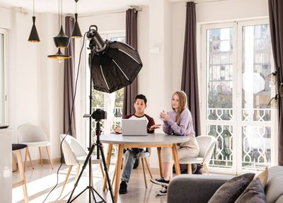 Video bloggers making a YouTube video with a professional camera on a tripod at home.