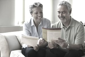 Elderly couple reading pamphlet on sofa