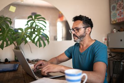 An investor takes a look at stock prices on laptop at home