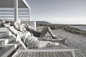 A couple relax in lounge chairs on a wooden deck as the sun shines on them.