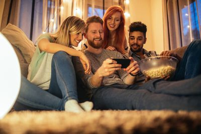Four young people sitting on the floor watch a streaming show on middle man's phone in his hand.