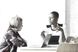Woman on a tablet talking seriously to a woman with a laptop in front of her