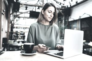 Woman using her credit card while browsing on a laptop