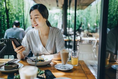 A woman uses her phone during a meal.