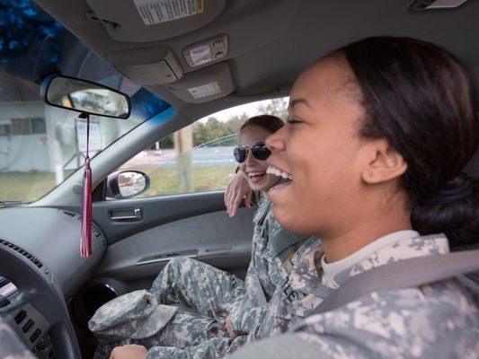 Two women in military uniforms laugh in the front seat of a car