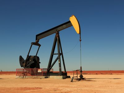 A photograph of working inland oil pump (oil donkey, nodding donkey) in the oil fields of West Texas, USA. Taken on a typical sunny day with blue skies.