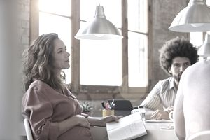 A pregnant woman at a table holds a notebook as she plans where to find maternity leave insurance.