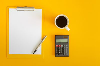Top-down view of a clipboard with a blank white sheet of paper, a calculator, and a cup of coffee on a yellow background.