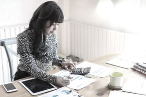 Businesswoman at her desk holding a pen.