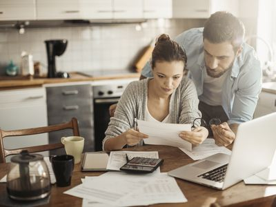 A couple looks over their HUD paperwork in their kitchen