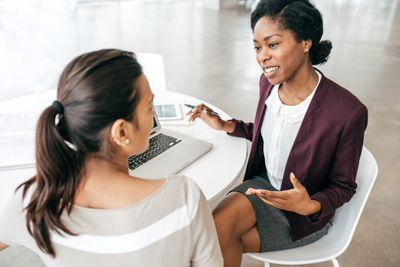 Two businesswoman talk at table with laptop and tablet