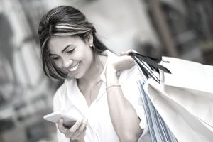 Woman with shopping bags looking at her phone and smiling