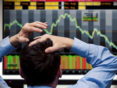 A commodities futures trader reacts to a strong downward spike and places his hands on his head.