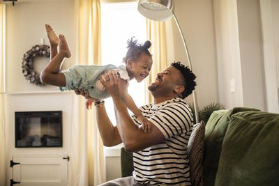 Father throws toddler daughter in the air in living room