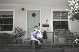 Man in suit sits on porch near for sale sign