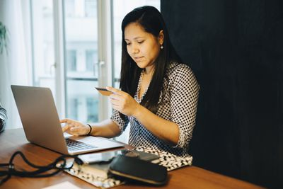 Woman holding credit card while shopping online on laptop while sitting at home