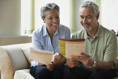 an older couple reading pamphlets on sofa