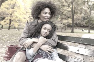A mother and daughter sitting on a park bench in fall