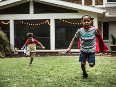 Young boys in capes playing in backyard
