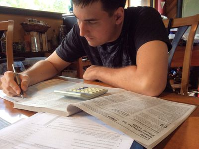 Young man filling out a tax form by hand with a calculator