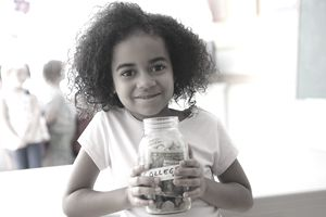 """young girl holding a clear glass jar of money with a label showing the word """"college"""""""