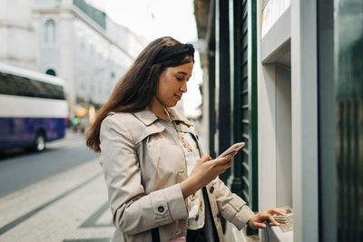 Woman using atm machine and mobile phone.