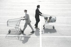 Two men in suits pushing shopping carts, symbolizing choosing different types of investments.