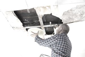Man catching water from a ruined ceiling in a bowl