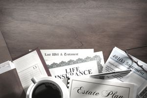 Estate plan, will, life insurance policy, and 401(k) statement on a table with coffee.