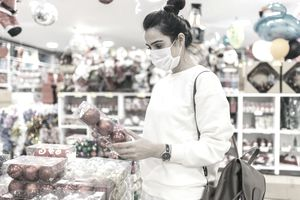 Woman wearing protective face mask and looking at a Christmas market stall - stock photo