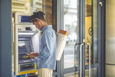 Young man uses ATM to conduct a bank transaction