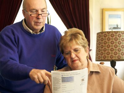 an older couple looking at documents to determine mandatory spending