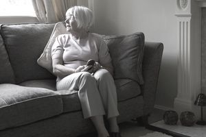 Elderly woman alone on the sofa holding a mobile phone