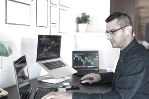 Man analyzing market charts on laptop computer screen at home office