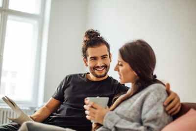 man and woman sitting on couch discussing finances