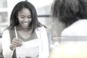 happy college student reading the financial aid reward letter to her mother