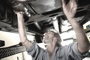 Mechanic is examining the catalytic converter of a car on a lift.
