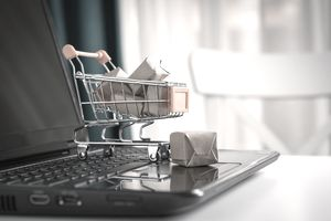 Miniature shopping cart full of packages sitting on a laptop keyboard showing online purchases